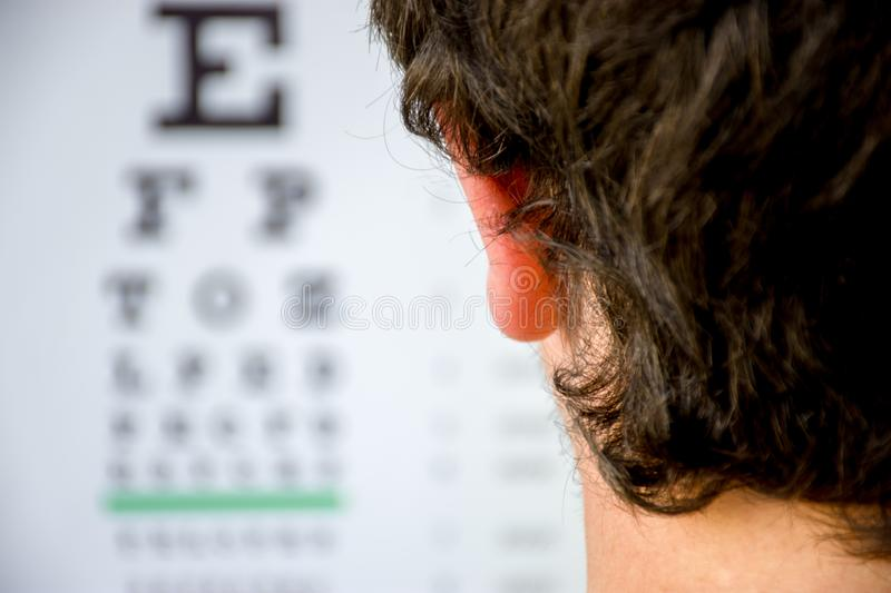 Concept photo of myopia or nearsightedness as diseases of eye and the optical system. In the background blurry fuzzy table for tes. Ting visual acuity, in the stock photo