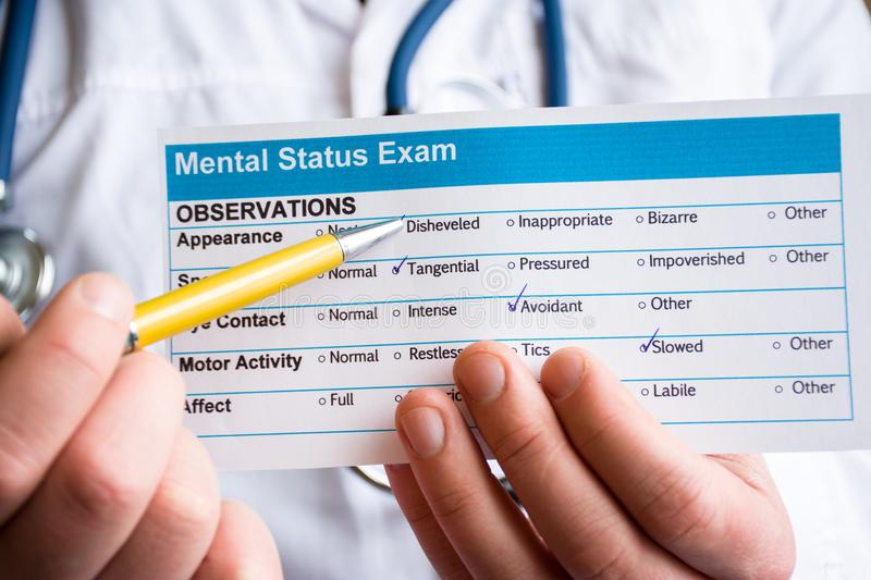 Concept photo psychiatric examination, assessment or consultation. Psychiatrist holds conclusion mental status exam and handle on. It in foreground. In stock photography