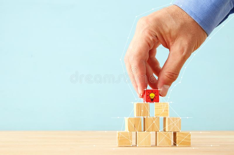 Concept photo of revealing an idea, finding the right solution during creative process. Hand picking piece of wooden block royalty free stock photo