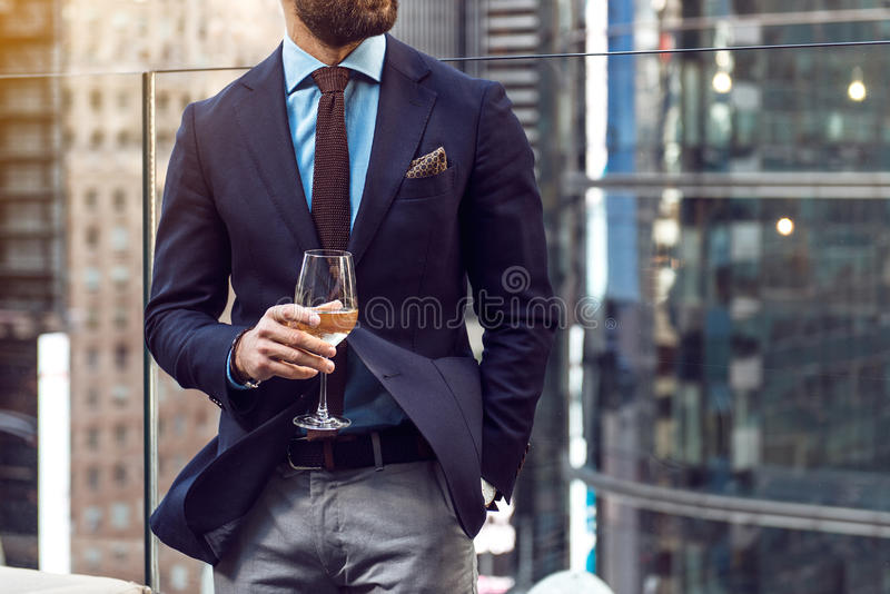 Concept photo of rich people luxury life. Adult successful elegant businessman wearing suit and drinking wine on the rooftop in lu stock photography