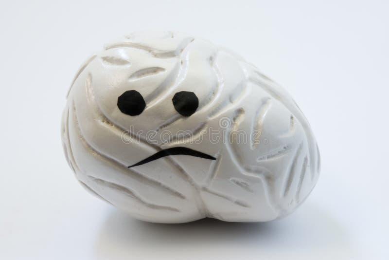 Concept photo of unhappy, sad brain with sickness disorder. Model of brain with sad smile, which symbolizes neurologic problem: di. Scomfort, headache, ache stock image