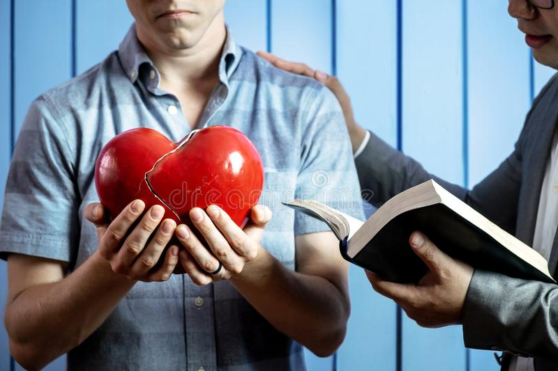 Concept Picture of a Caucasian Man with His Broken Heart and Healing from the Words of God by Pastor. royalty free stock photos