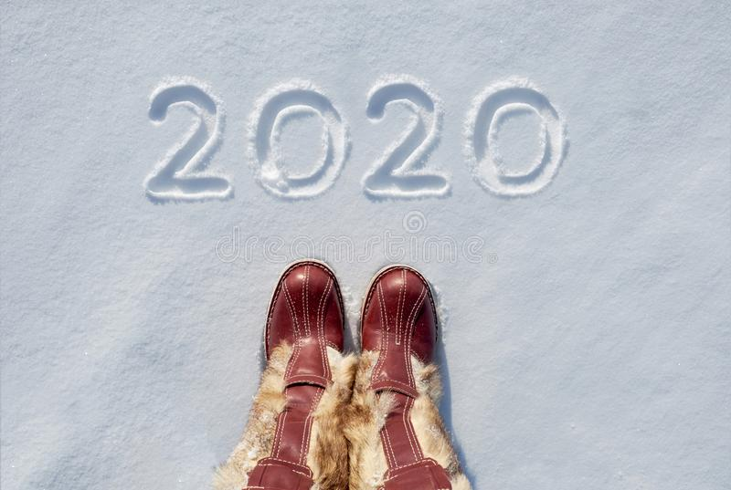 Concept picture.inscription New Year 2020 and footprints in the snow stock images