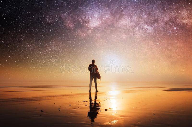 A concept picture of man holding a surfboard, silhouetted against the setting sun with stars and the universe overhead at night stock images