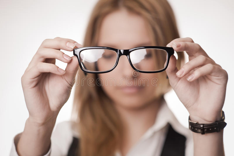 Concept: poor eyesight. Girl holding glasses, selective focus on glasses. Concept: poor eyesight stock photos
