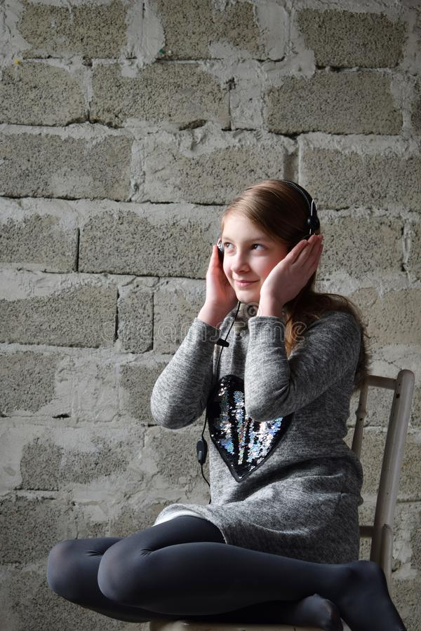 Concept portrait of a pleasant friendly happy teenager in headphones listening to music. Young girl is sitting in a gray dress and royalty free stock photos