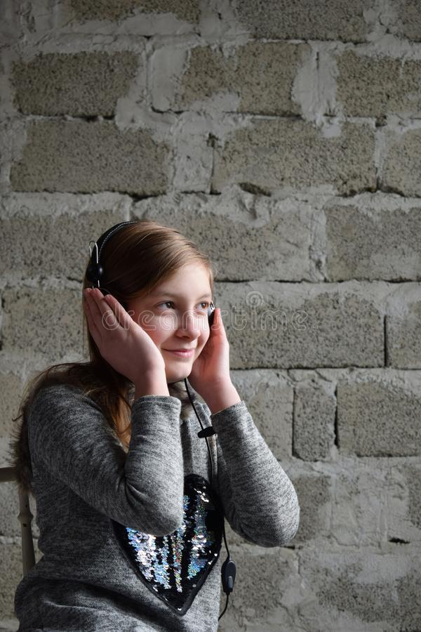 Concept portrait of a pleasant friendly happy teenager in headphones listening to music. Young girl is sitting in a gray dress and royalty free stock photo