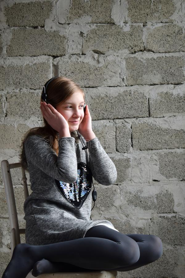 Concept portrait of a pleasant friendly happy teenager in headphones listening to music. Young girl is sitting in a gray dress and stock photos