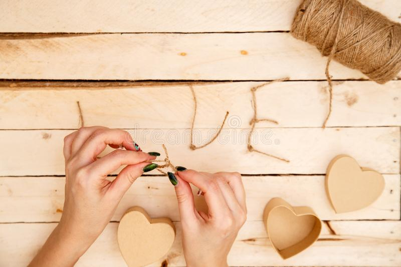 Concept pour des histoires d'amour et pour la Saint-Valentin Les mains femelles font des boîtes sous forme de coeur et d'inscript image stock