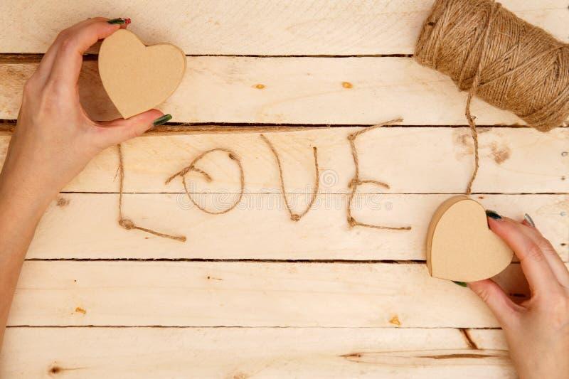Concept pour des histoires d'amour et pour la Saint-Valentin Les mains femelles font des boîtes sous forme de coeur et d'inscript photo libre de droits