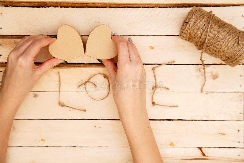 Concept pour des histoires d'amour et pour la Saint-Valentin Les mains femelles font des boîtes sous forme de coeur et d'inscript images libres de droits