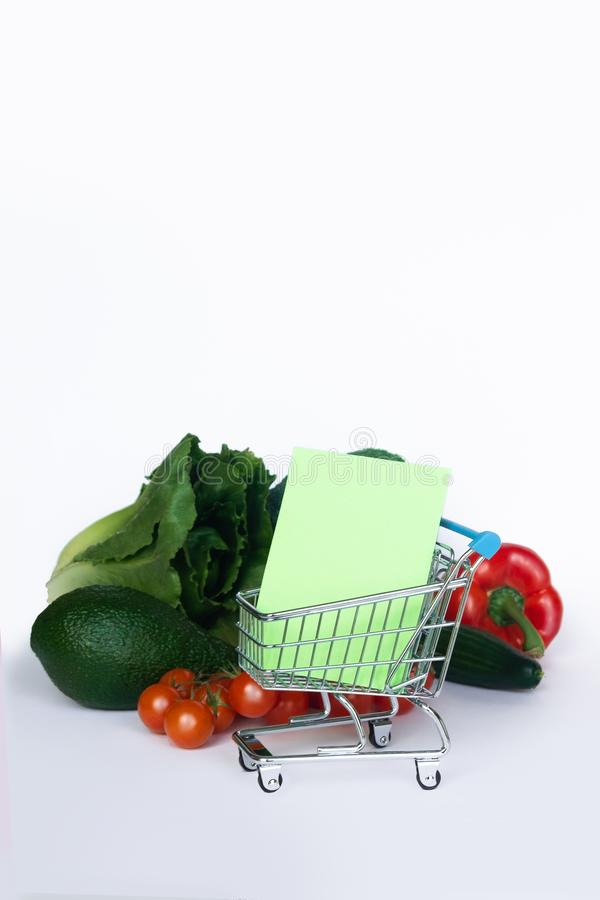 Concept pour l'achat Chariot avec la liste d'achats et différents légumes sur le fond blanc Copiez l'espace photo libre de droits