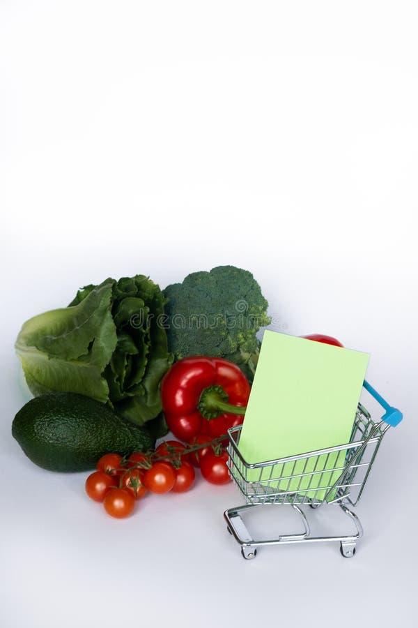 Concept pour l'achat Chariot avec la liste d'achats et différents légumes sur le fond blanc Copiez l'espace photo stock