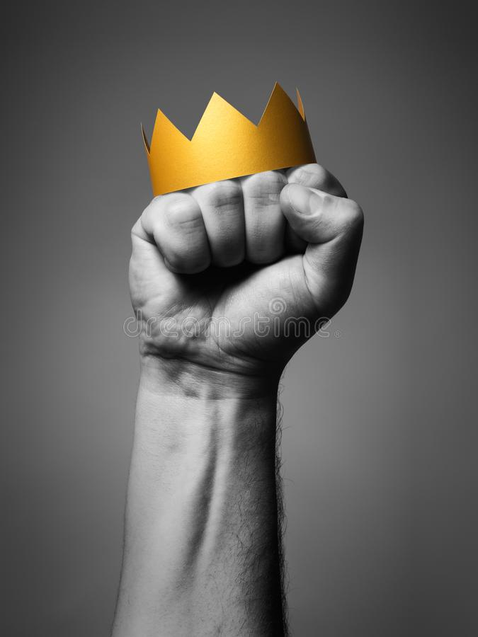Concept of power. Golden crown on a man`s fist. Black and white stock photography