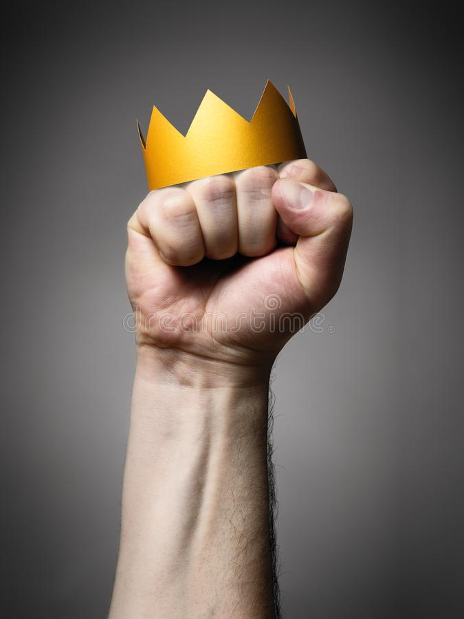 Concept of power. Golden crown on a man`s fist stock photos