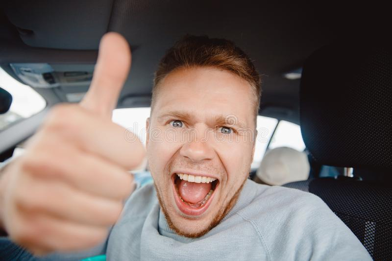 Concept preparing for road trip, auto rental. Happy man driver buyer car looking camera and taking selfie photo stock photo