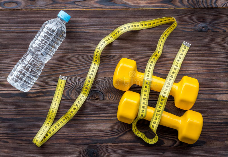 Concept preparing to fitness sports equipment top view. On wooden background royalty free stock photo