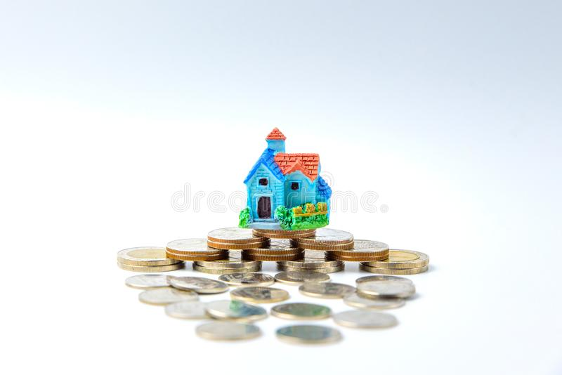 Concept for property ladder, mortgage and real estate investment. House modell on top of coins stack royalty free stock images