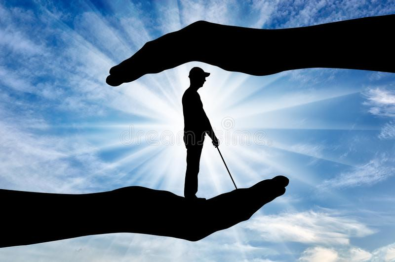 Concept of protection and assistance to blind disabled people. Silhouette of a blind disabled man with a cane in hand of help. The concept of protection and royalty free stock photography