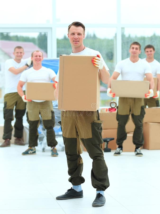 Foreman and workers with boxes of building materials stock photography