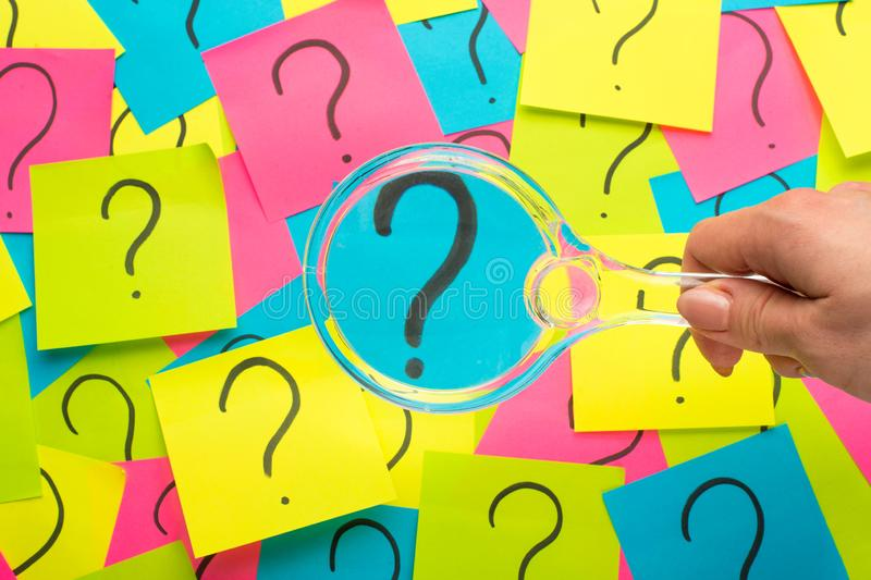 Concept with question mark on sticky note and magnifying glass royalty free stock images