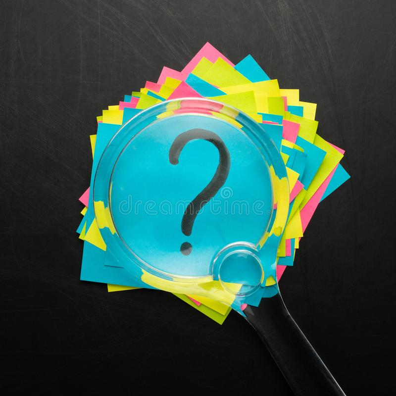 Concept with question mark on sticky note and magnifying glass royalty free stock photos