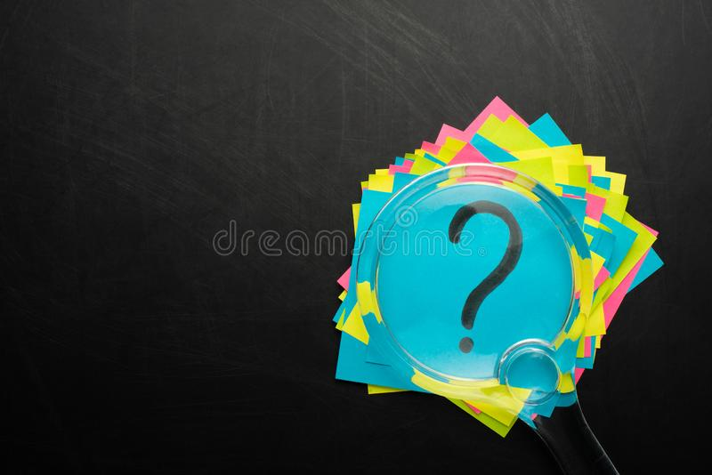 Concept with question mark on sticky note and magnifying glass stock image