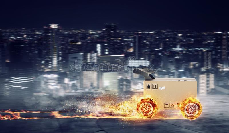 Priority Cardboard box with racing wheels on fire. Fast shipping by road. royalty free stock images