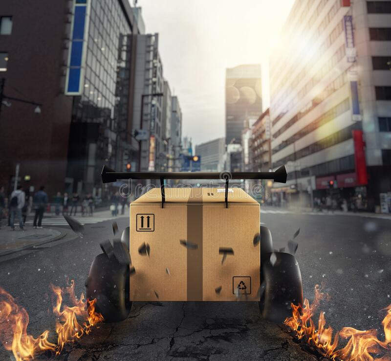 Priority Cardboard box with racing wheels that run in the city like a car. Fast shipping by road. stock photos