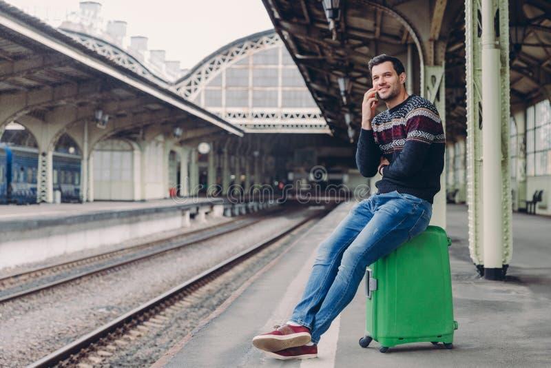Concept quotidien de mode de vie L'homme bel utilise le chandail et les jeans, pose à la plate-forme de gare, se penche au sac, a photographie stock