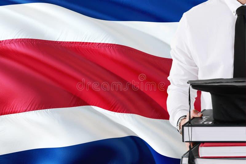 Concept réussi d'éducation d'étudiant Tenir les livres et le chapeau d'obtention du diplôme au-dessus du fond de drapeau de Costa photographie stock