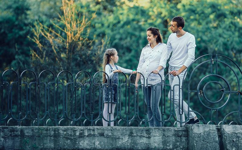 Concept of raising children - a little girl with a pregnant moth. Little girl with a pregnant mother,a happy father standing on the bridge on a walk in the Park royalty free stock images
