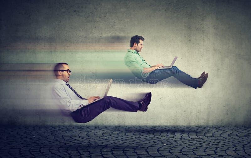 Concept rapide d'Internet Deux hommes faisants de la lévitation d'affaires sur la route utilisant photos stock