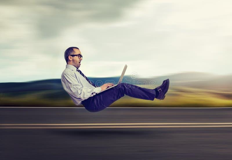Concept rapide d'Internet Homme faisant de la lévitation d'affaires sur la route utilisant l'ordinateur portable photo stock