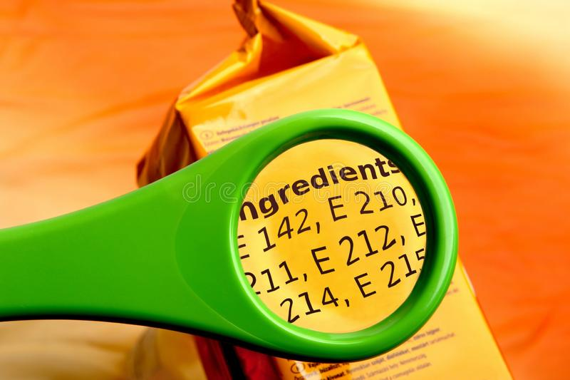 Concept of reading ingredients list on food package with magnifying glass. Magnifying glass on food additives label stock photo