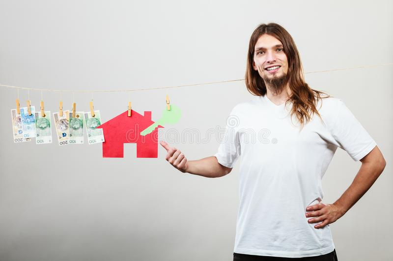 Man seller with money and house. Concept of real estate and deal. Seller man with house model and banknotes. Selling and buying proposition stock image