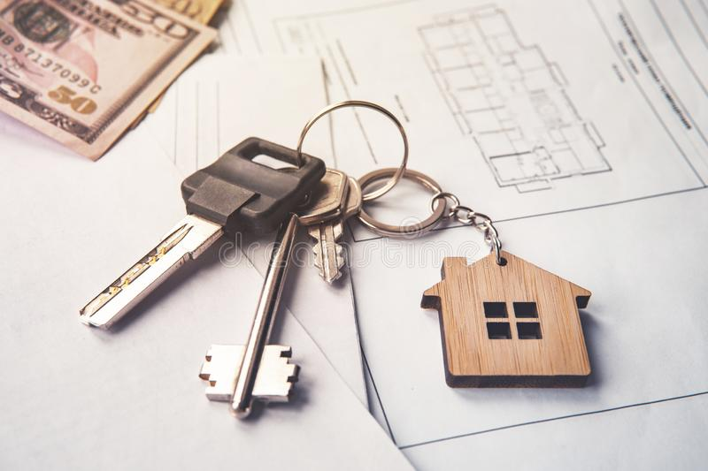 concept of real estate sale or lease. Keys with keychain and American dollars in the form of a house lying on a paper with a plan royalty free stock images