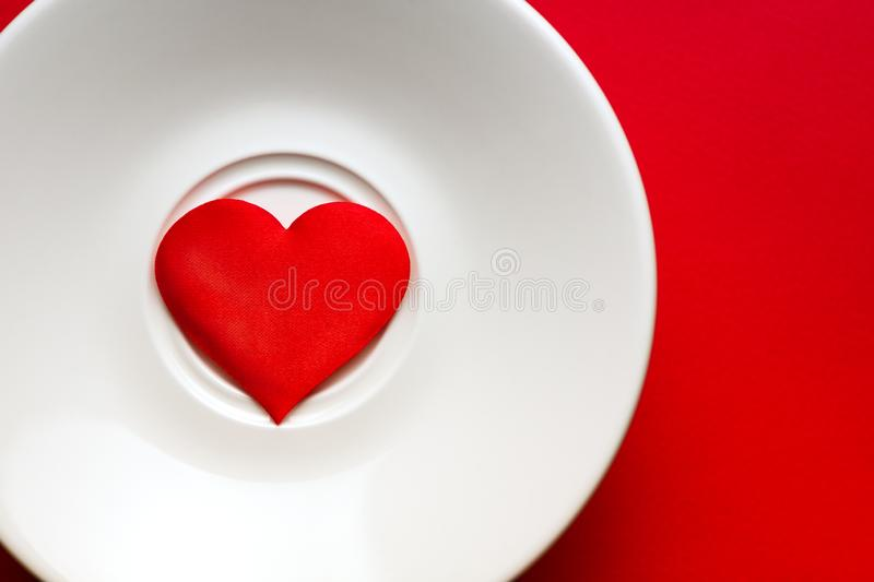 Concept red heart at white dish. greeting card. copy space. relationships and humans. healthy lifestyle. royalty free stock photo