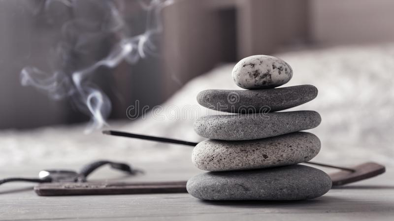 Concept of relax or meditation. Pyramid of zen stones, burning incense stick, bedroom interior. stock photography