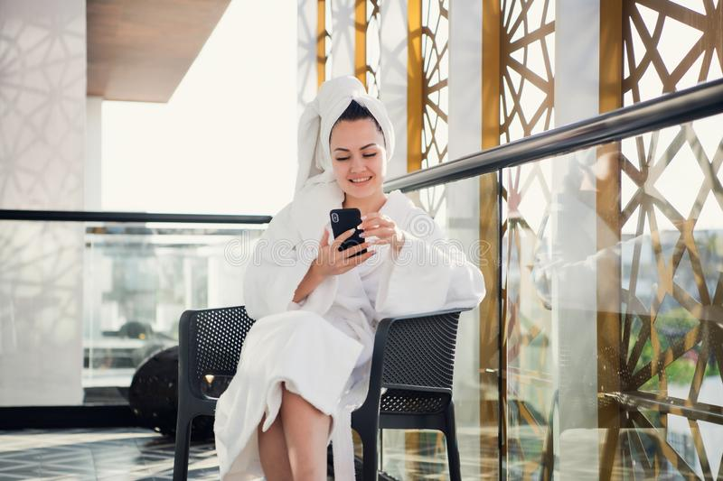 Concept of relaxation and communication after spa. Portrait of young lady in bathrobe talking by phone on terrace royalty free stock photos