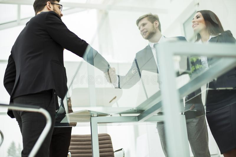concept of a reliable partnership : a handshake of business partners on the background of the workplace royalty free stock images