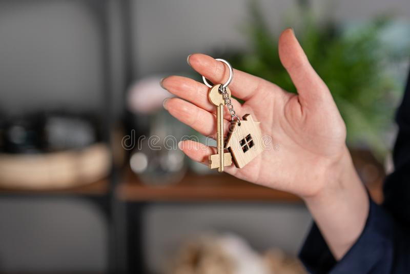 Concept of renting an apartment. House key in womans hands. Young woman. Modern light lobby interior. Real estate stock photos