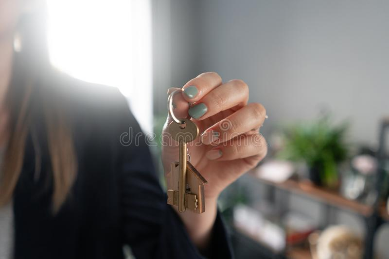 Concept of renting an apartment. House key in womans hands. Young woman. Modern light lobby interior. Real estate. Hypothec, moving home or renting property royalty free stock photo
