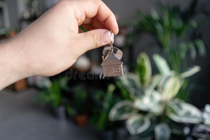 Concept of renting an apartment. House key in man hands. Young woman. Modern light lobby interior. Real estate, hypothec. Concept of renting an apartment. House stock images