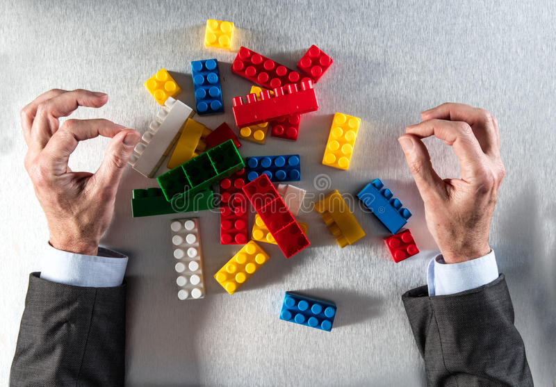 Concept of reorganization with zen businessman hands facing messy group. Concept of reorganization or restructuring with zen businessman hands facing a group of stock photography