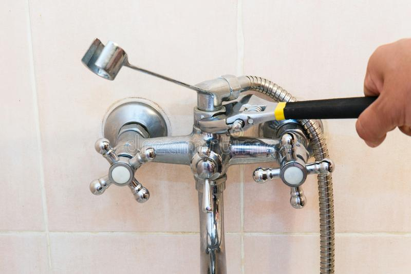 The concept of repair and replacement of the mixer in the bathroom. Old faucet mixer in the bathroom.  stock photography