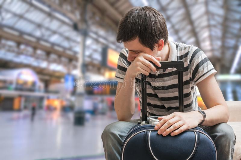 Concept retardé de train Le passager fatigué s'assied dans la station de train images stock