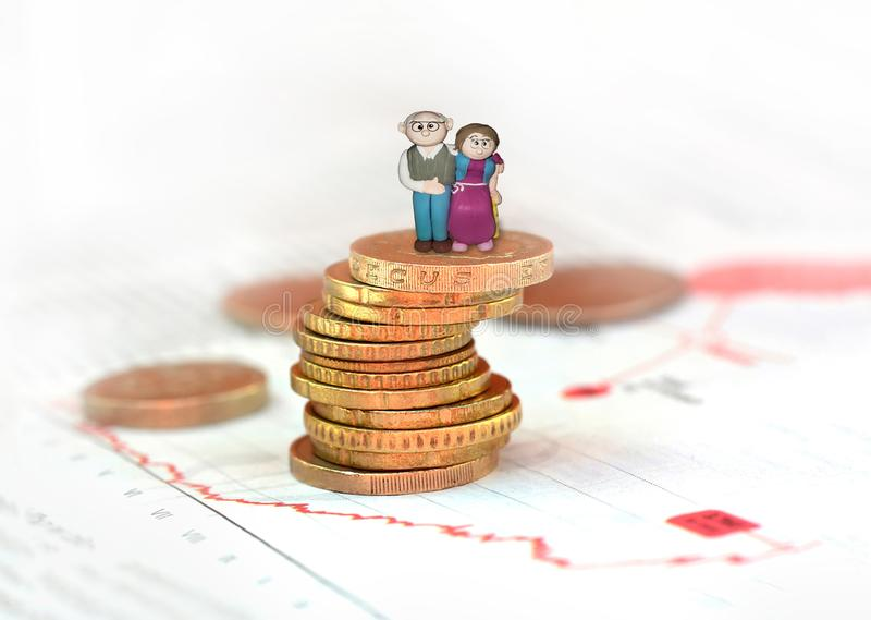 Concept of retirement planning. Old couple figure standing on top of coin stack royalty free stock image