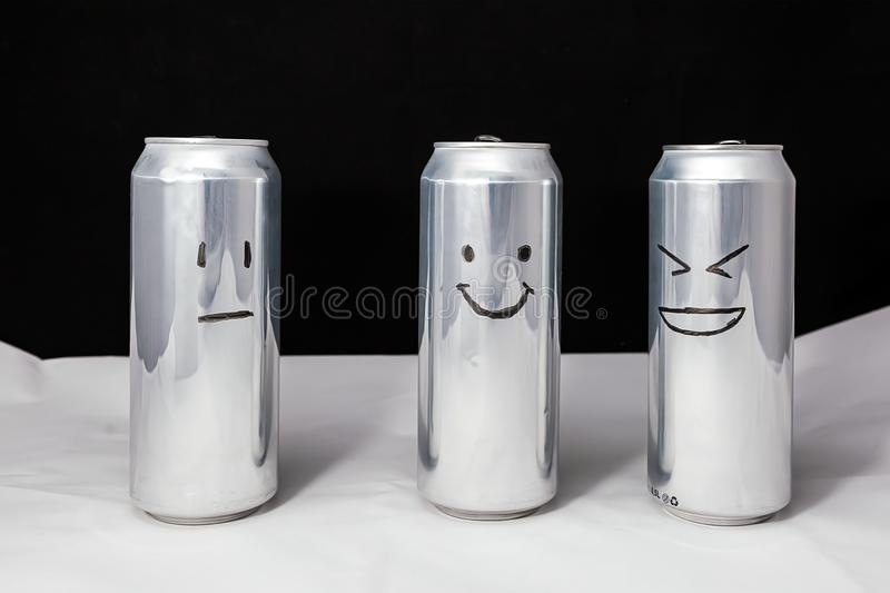 Concept of ridicule. Joke over a friend but it`s not funny to him. Aluminium cans with drowing emoticons. Emoji of laugh, smile. And no emotions royalty free stock photos