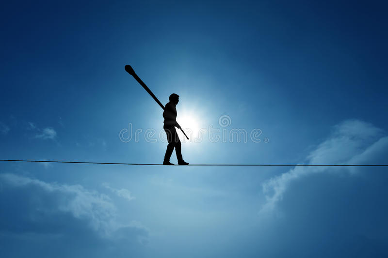 Concept of risk taking and challenge highline walker in blue sky stock image
